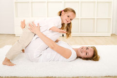 Little girl and woman playing indoors on the floor Stock Photos