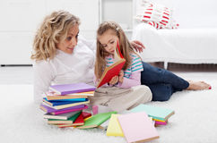 Little girl and woman reading together Stock Photo