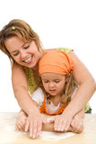 Little girl and woman stretching the dough Stock Images