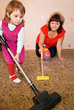 Little Girl and woman vacuum a carpet Royalty Free Stock Photos