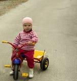 Little girl wondering. Little girl on bike looking sceptical stock photo