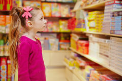 Little girl wonderingly looks on abundance of board games Stock Images
