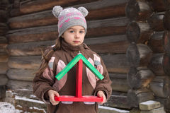 Little girl with a wooden bird feeder in winter Royalty Free Stock Image