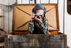 Little girl in wooden chest taking ptoto with rarity camera Stock Image