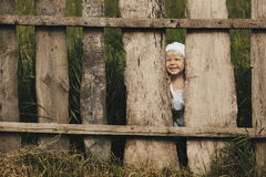 Little girl and wooden fence Stock Images