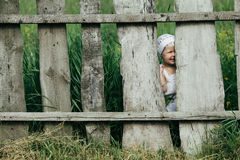 Little girl and wooden fence Stock Photos