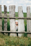Little girl and wooden fence Royalty Free Stock Image