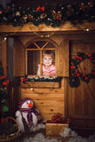 Little girl in wooden house with christmas decoration Stock Photography