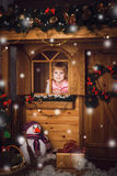 Little girl in wooden house with christmas decoration Stock Images