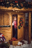 Little girl in wooden house with christmas decoration Royalty Free Stock Images