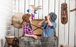 Little girl with wooden plane in hand and boy in pilot hat Royalty Free Stock Images