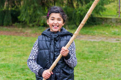 Little girl with wooden pole playing fight smiling royalty free stock photo