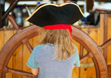 Little girl with wooden ship's wheel. Stock Photo