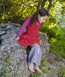 Little girl in woods. Little girl sitting on a rock in the woods Stock Photos