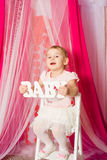 Little girl with a  word baby in pink  skirt Stock Photography