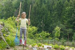 Little girl working in the garden. Little girl holding gardening tools, having fun in the garden, planting, gardening, helping her mother. Happy, natural stock images