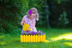 Little girl working in the garden watering flowers Royalty Free Stock Photo