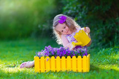 Little girl working in the garden watering flowers Royalty Free Stock Photos
