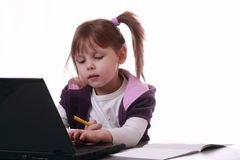 A little girl is working with a laptop Stock Photography