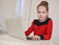 Little girl working on laptop sitting at the table Stock Photography