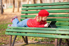 Little girl working with tablet pc in the park. Happy smiling little girl working with tablet pc and lying on bench in the park royalty free stock photo