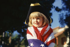 Little girl wrapped in American flag,. Wearing hat Royalty Free Stock Photo
