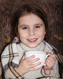Little girl wrapped in a blanket drinking a cup of warming beverage. Stock Photos