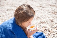 Little child wrapped in blue towel drinking cup of tea on summer beach outdoor Royalty Free Stock Photography