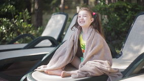 A little girl wrapped in a towel sits on a lounger by the pool and basks in the sun stock video