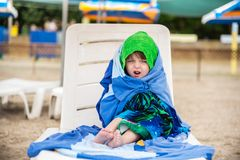 The little girl wrapped in towels for warming, facial expression royalty free stock photos
