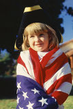 Little Girl Wrapped in U.S. flag. Little girl wrapped in American flag wearing three cornered hat Stock Photos