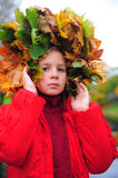 The little girl with a wreath from autumn leaves Stock Photo