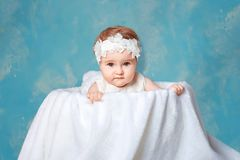 A little girl with a wreath on her head sitting in a large basket stock photography