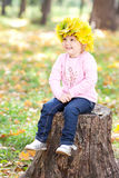 Little girl in a wreath of maple leaves Royalty Free Stock Photos