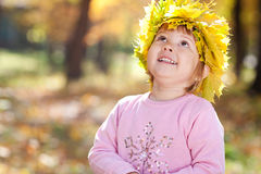 Little girl in a wreath of maple leaves Stock Photos