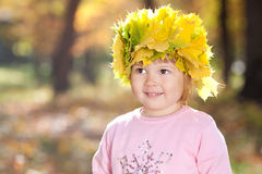 Little girl in a wreath of maple leaves Royalty Free Stock Images