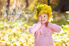 Little girl in a wreath of maple leaves Royalty Free Stock Photo
