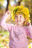Little girl in a wreath of maple leaves Royalty Free Stock Image