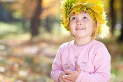 Little girl in a wreath of maple leaves in autumn fore Stock Photos
