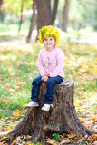 Little girl in a wreath of maple leaves in autumn fore Stock Images