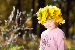 Little girl in a wreath of maple leaves in autumn fore Stock Image