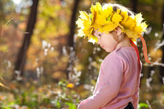 Little girl in a wreath of maple leaves in autumn fore Royalty Free Stock Photo