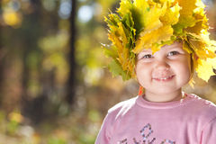 Little girl in a wreath of maple leaves in autumn fore Royalty Free Stock Photography
