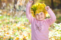 Little girl in a wreath of maple leaves in autumn fore Royalty Free Stock Images