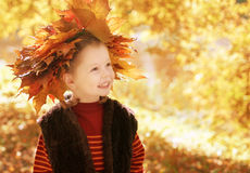 Little girl with wreath of  maple leaves standing Stock Photos