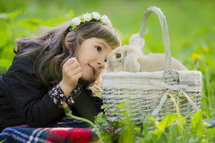 A little girl in a wreath observes a rabbit in a basket at sunset in a park. Stock Image