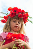 Little girl in a wreath from poppies. Little girl's portrait in poppies Royalty Free Stock Image