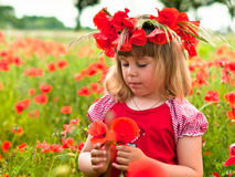 Little girl in a wreath from poppies. Little girl's portrait in poppies Royalty Free Stock Photos