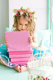 Little girl with wreath and stack of books Stock Photography