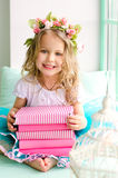 Little girl with wreath and stack of books Stock Images